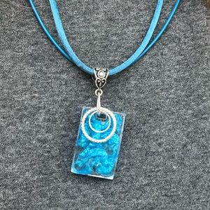 Jewelry - Clear resin and blue metallic powder necklace .